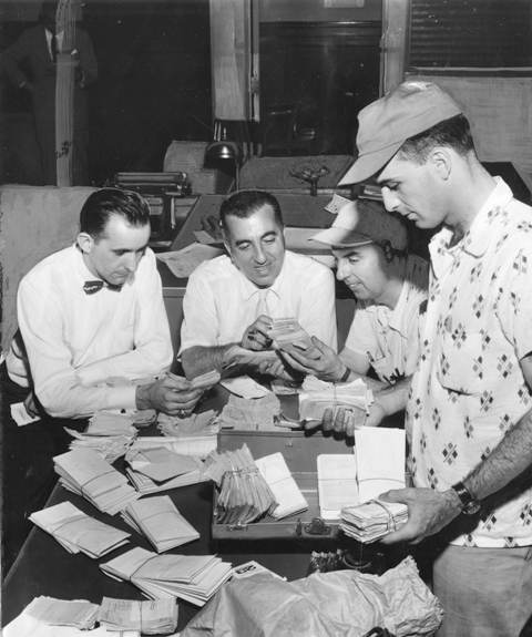 Philadelphia detectives examining receipts from an illegal gambling house, 1955.